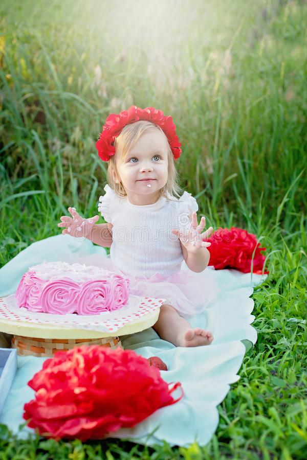 Second birthday of little girl. Two years old girl sitting near celebration decorations and eating her birthday cake. Cake Smash. Baby, cute, child, park, fun royalty free stock image