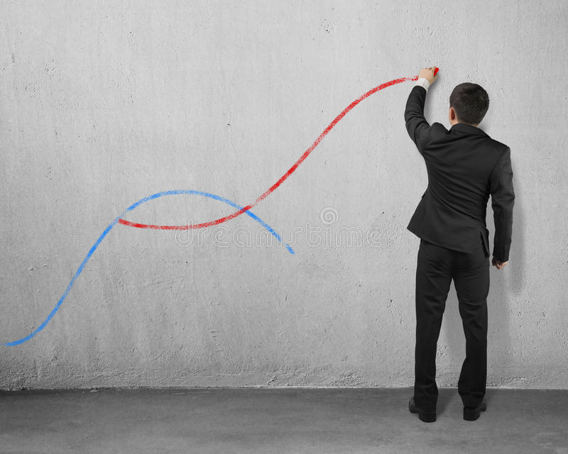 The second curve concepts. Man holding chalk drawing two curves on concrete wall stock image