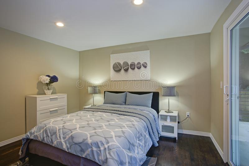 Second floor bedroom with taupe walls, blue bed. And private balcony stock photos