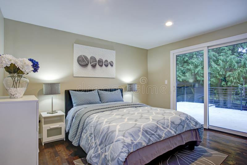 Second floor bedroom with taupe walls, blue bed. And private deck stock images
