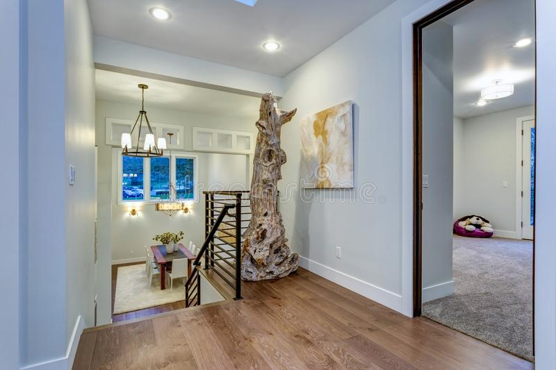Second floor landing with white walls. Maple hardwood floor and a driftwood statue next to an abstarct art piece on the wall royalty free stock photography