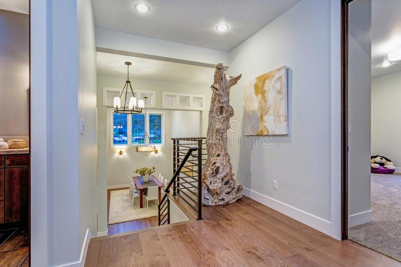 Second floor landing with white walls. Maple hardwood floor and a driftwood statue next to an abstarct art piece on the wall stock photography