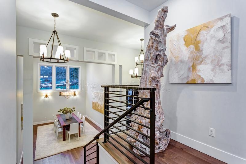 Second floor landing with white walls. Maple hardwood floor and a driftwood statue next to an abstarct art piece on the wall royalty free stock photos