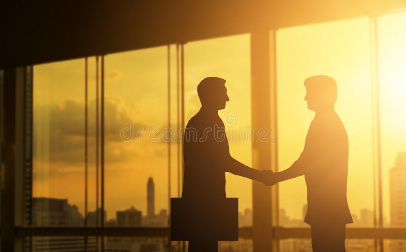 Second hand business hand in concept office silhouettes and successful business partner. royalty free stock photo
