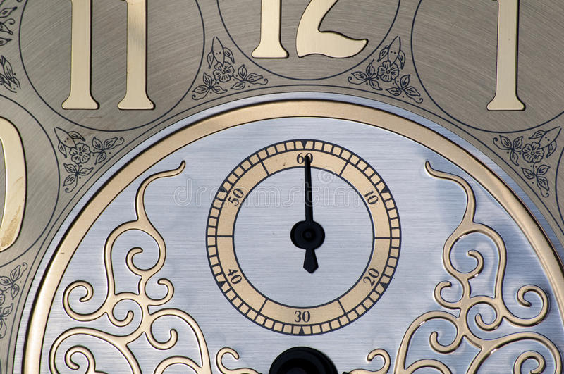 Second hand on clock face. Close-up of shiny brass clock face showing the second hand, which is straight up on the 60. The picture also shows part of the 11, 12 royalty free stock photography