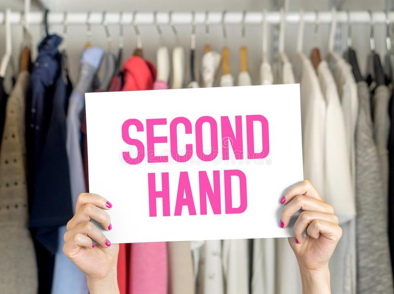 Second hand clothing. Shop. Woman holding sales banner in store royalty free stock photo