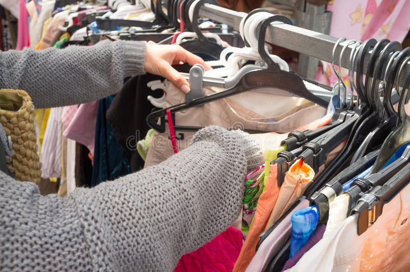 Second hand shop market. Female hands rummaing in clothes in a second hand shop stock photography
