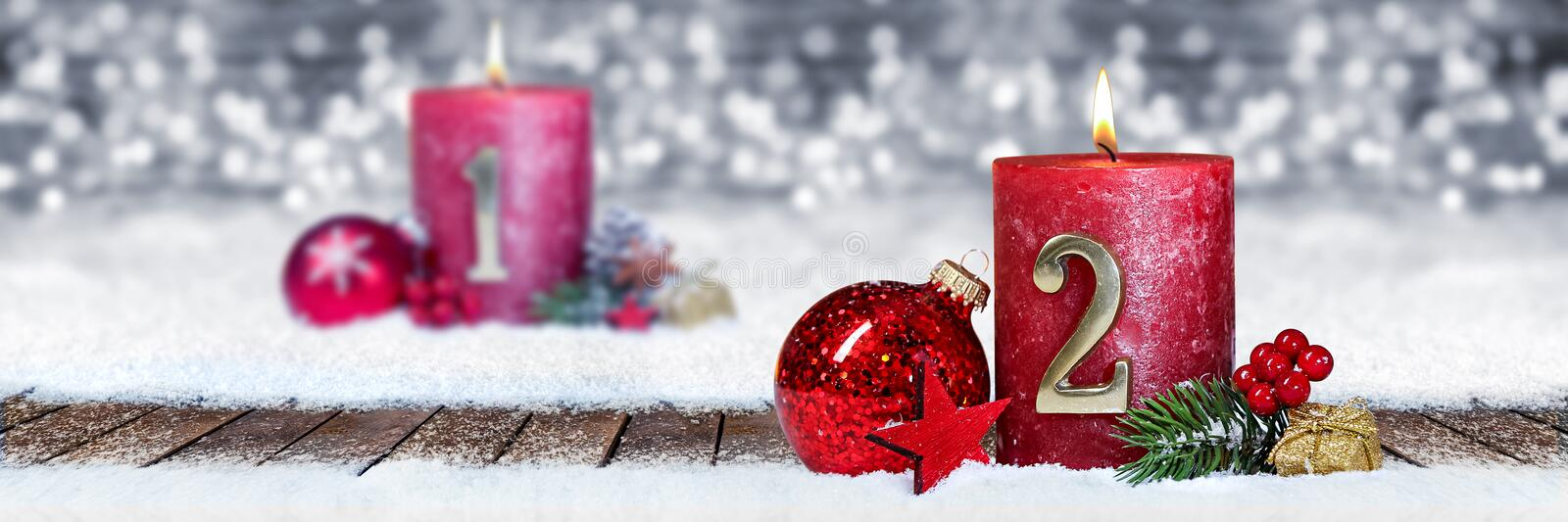 Second sunday of advent red candle with golden metal number one on wooden planks in snow front of panorama bokeh background. Second sunday of advent red candle stock images
