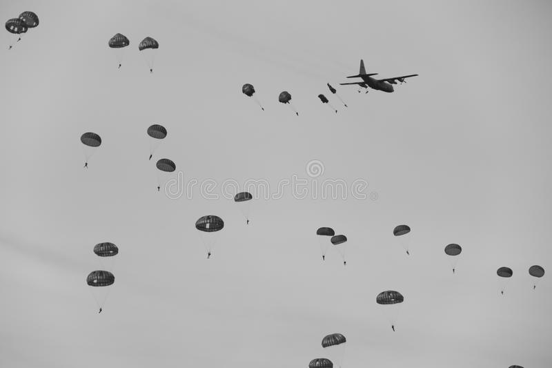 Second world war mass dropping paratroopers. Second world war soldiers jumping out of an airplane above the ginkelse heide during the memorial day of operation royalty free stock photo
