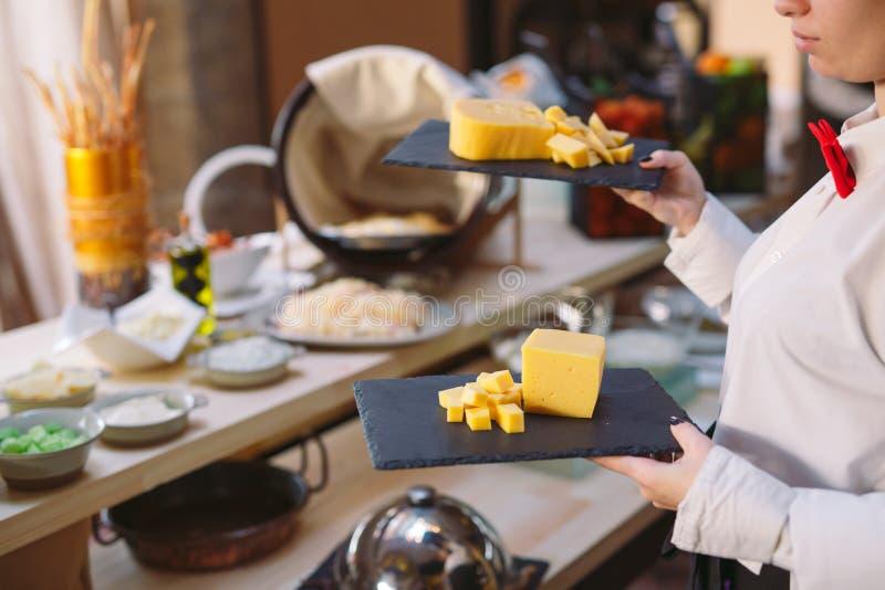 secouez Le serveur tient un plat de fromage coupé en tranches photographie stock