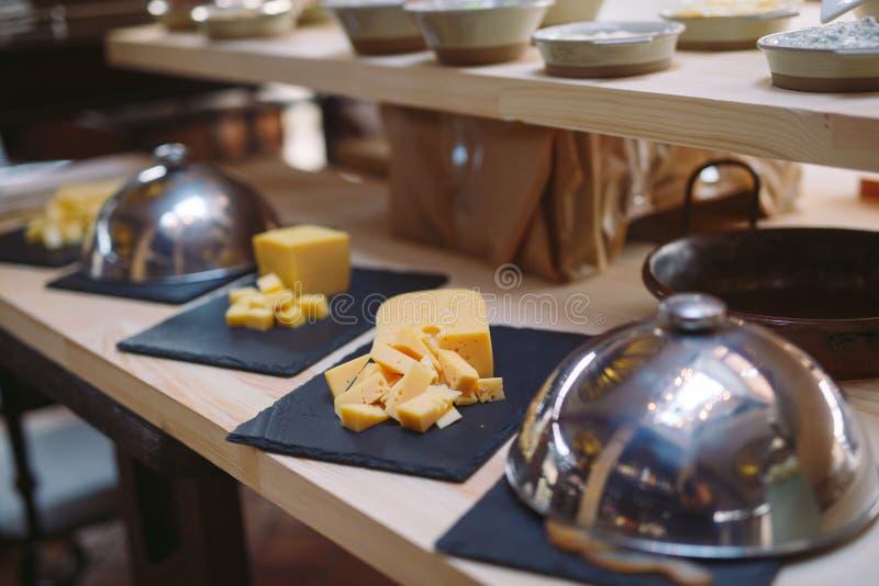secouez Le serveur tient un plat de fromage coupé en tranches photo stock