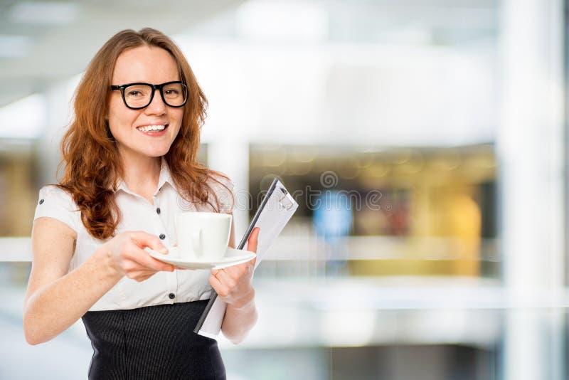 secrétaire assez jeune avec une tasse de café photos libres de droits