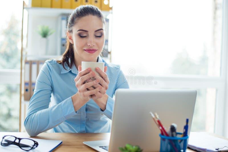 Secrétaire de sourire s'asseyant à la table jugeant la tasse de café image stock