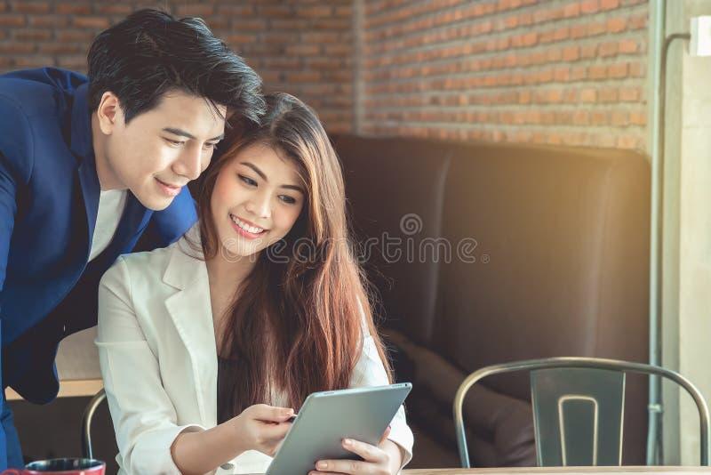 Secrétaire et homme d'affaires féminins Asians regardent l'informati photo libre de droits