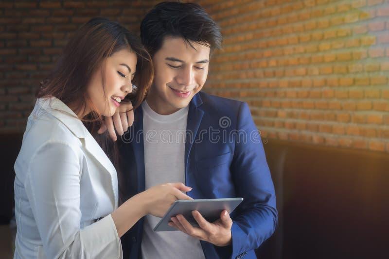 Secrétaire et homme d'affaires féminins Asians regardent l'informati images stock