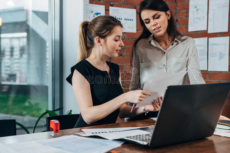 Secrétaire féminin regardant concerné tandis que son patron vérifiant le document se reposant le bureau dans le bureau moderne images stock