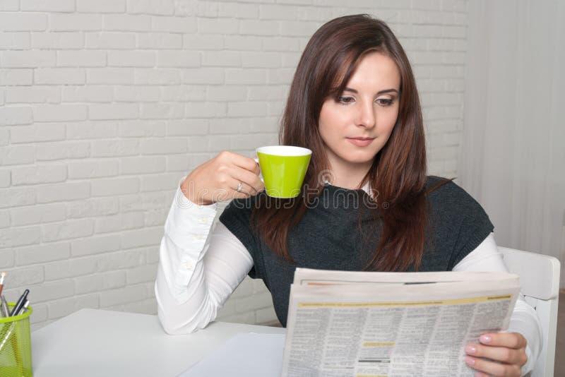Secrétaire Girl lisant un journal le tenant dans une main image libre de droits