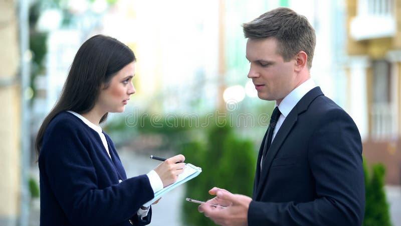 Secretária do sexo feminino registrando as ordens dos macho do notebook, assistente pessoal fotografia de stock royalty free