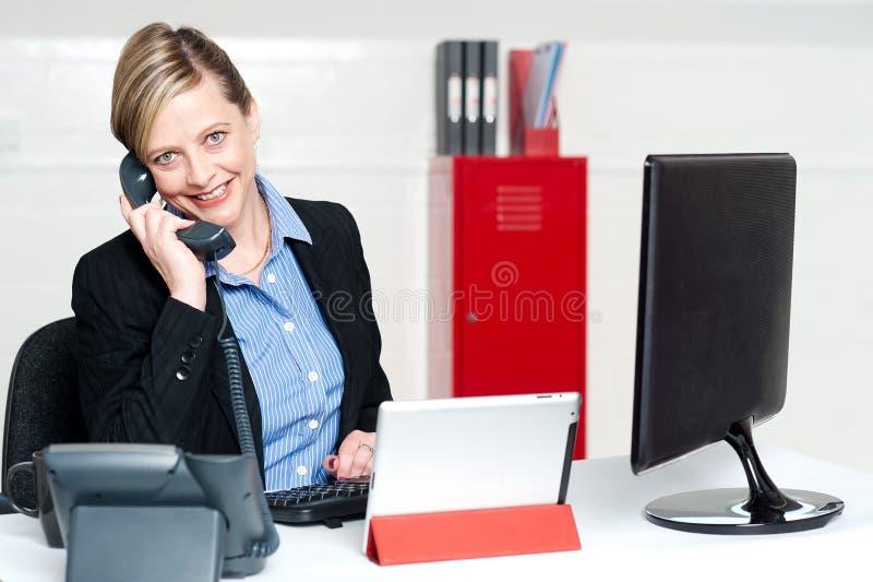 Secretária fêmea de sorriso que atende ao atendimento de telefone fotos de stock