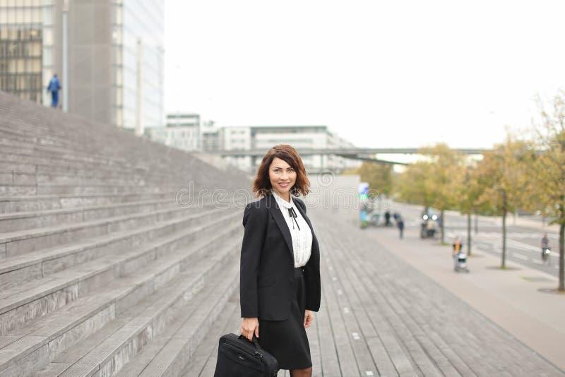 Secretário caucasiano fêmea que está em escadas com saco e em construções altas no fundo fotos de stock royalty free
