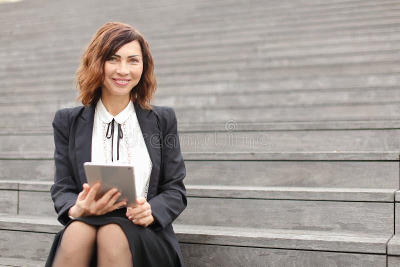Secretário de sorriso fêmea que senta-se em escadas com tabuleta e trabalho imagens de stock