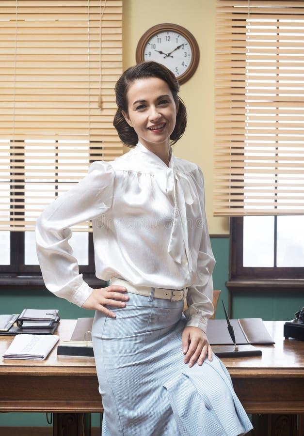 Secretário de sorriso que inclina-se na mesa fotografia de stock royalty free