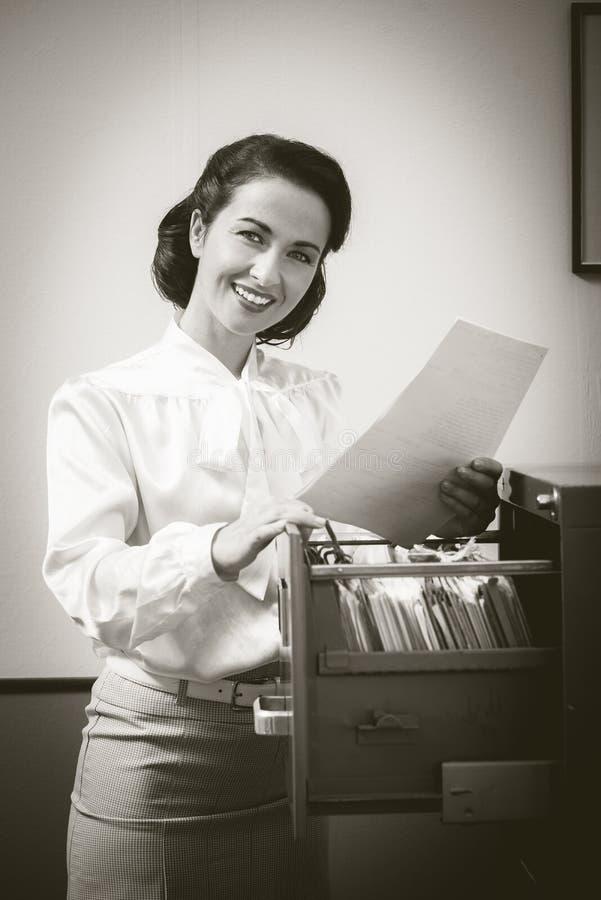 Secretário de sorriso que procura arquivos no arquivo foto de stock