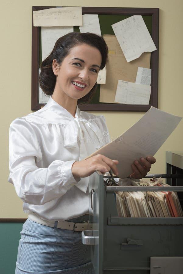 Secretário de sorriso que procura arquivos no arquivo imagem de stock