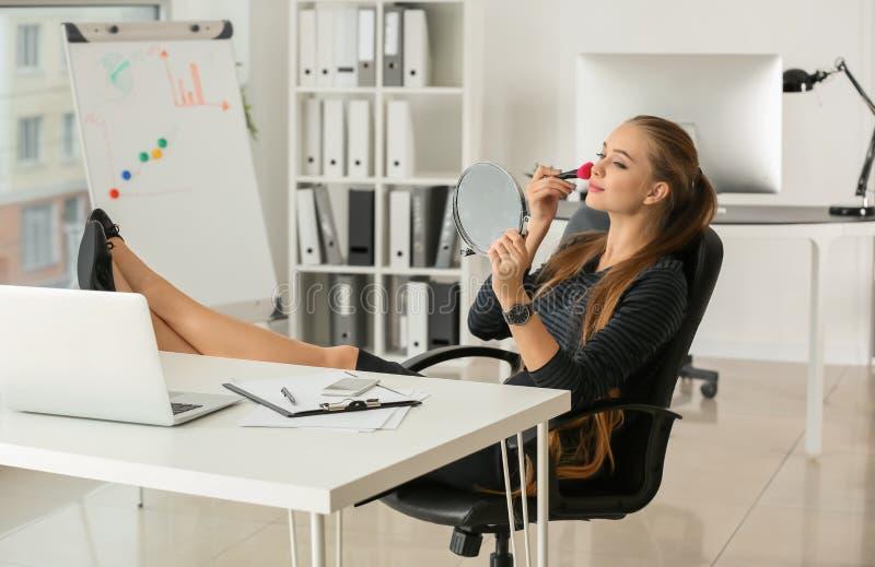 Secretário fêmea bonito que aplica a composição no escritório fotografia de stock royalty free
