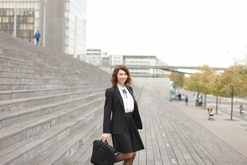 Secretário fêmea que está em escadas com saco e em construções altas no fundo foto de stock royalty free