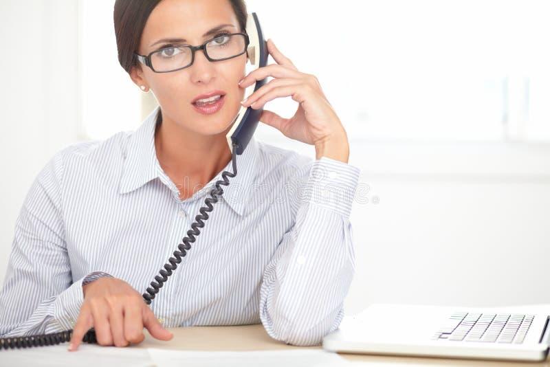 Secretário latino que faz o serviço ao cliente no escritório fotos de stock royalty free