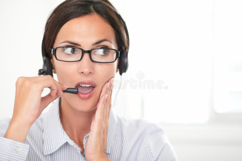 Secretário moreno que fala em seus auriculares imagens de stock