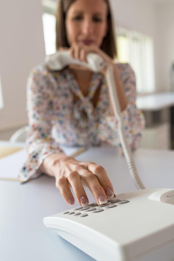 Secretário novo que senta-se em sua mesa de escritório que disca um número de telefone imagem de stock royalty free