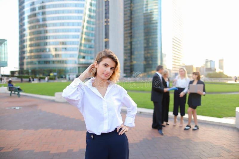 Secretário que olha a câmera com fundo dos membros da equipa no La D foto de stock