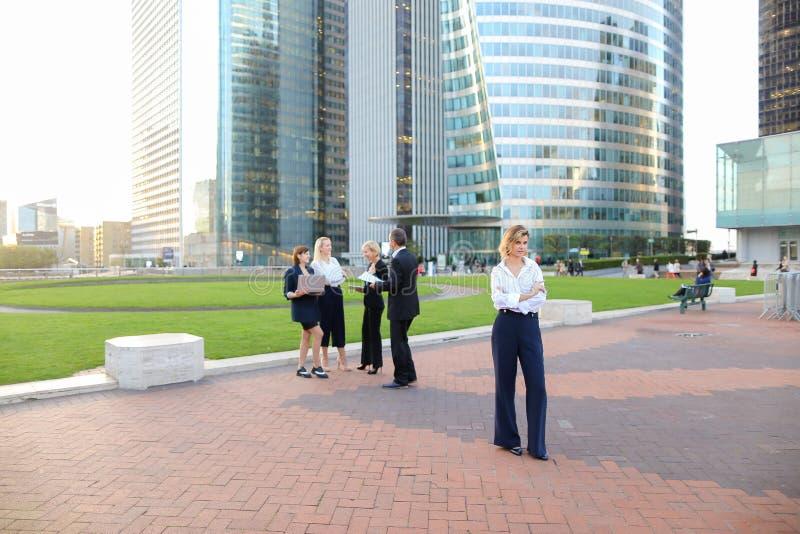 Secretário que olha a câmera com fundo dos membros da equipa no La D fotos de stock royalty free