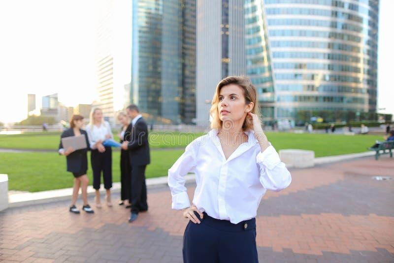 Secretário que olha a câmera com fundo dos membros da equipa no La D imagem de stock royalty free