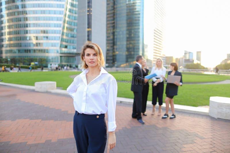 Secretário que olha a câmera com fundo dos membros da equipa no La D fotografia de stock royalty free