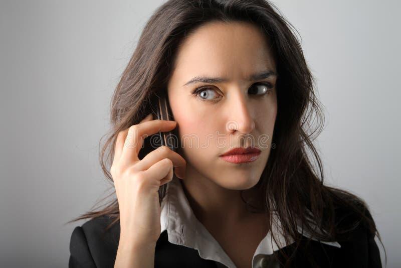 Secret. Businesswoman with mobile phone listening a secret stock photo