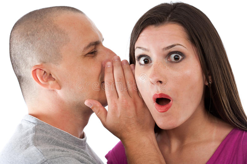 The Secret. Man whispering a secret to a surprised young lady stock photo