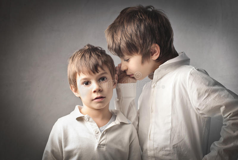 Secret. Child telling a secret to his little brother stock photography