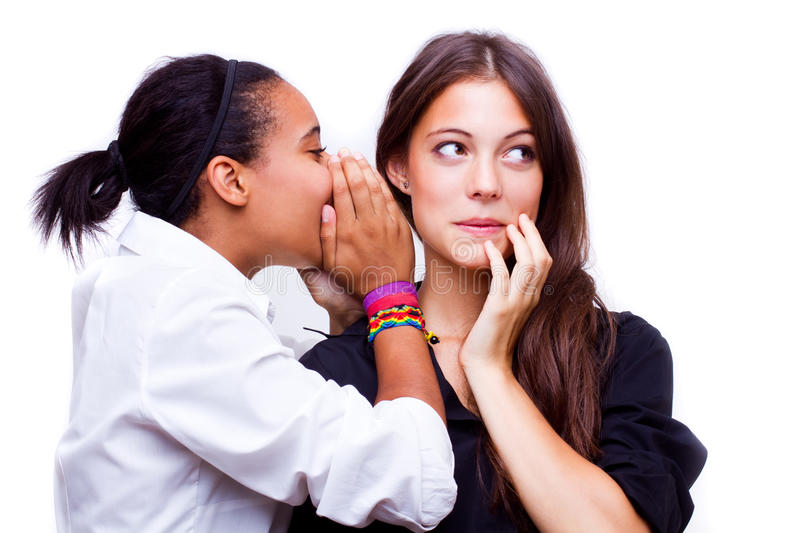 Secret. Portrait of young african american women telling a secret to a caucasian women over a white background royalty free stock photo