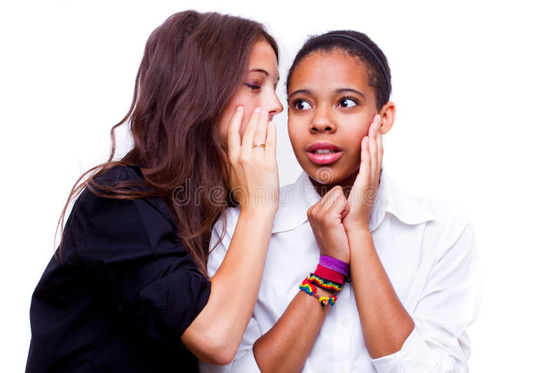 Secret. Portrait of young caucasian women telling a secret to an african american women over a white background stock photography