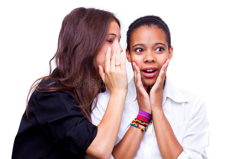 Secret. Portrait of young caucasian women telling a secret to an african american women over a white background royalty free stock images