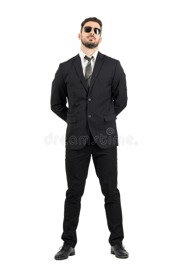 Secret agent or guard with hands behind back wearing sunglasses royalty free stock image
