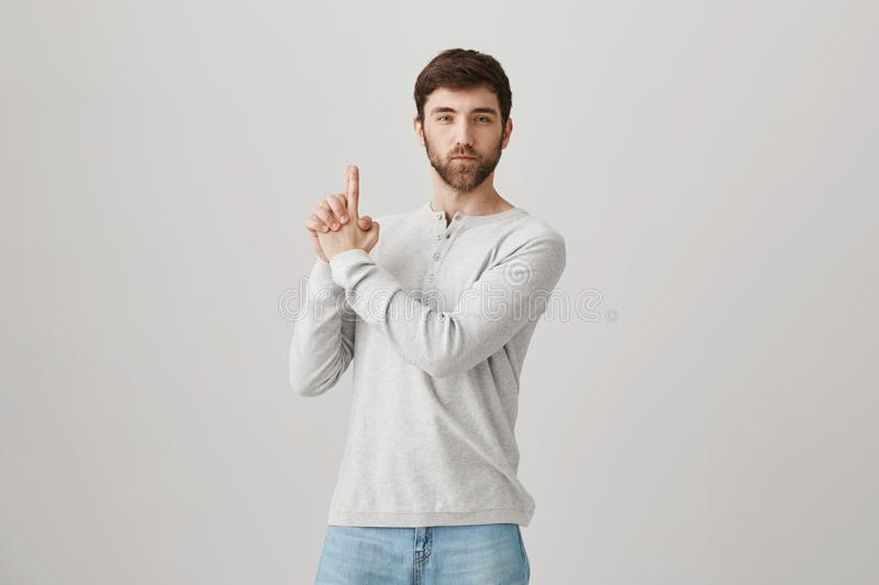 Secret agent ready to protect peace. Portrait of attractive funny mature man with beard showing raised gun gesture as if royalty free stock photo