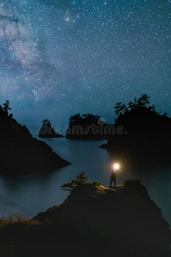 Secret Beach Oregon at Night with Stars and hiker Standing with the Light. This is the picture of Secret Beach Oregon at Night with Stars and Traveler Standing stock photos