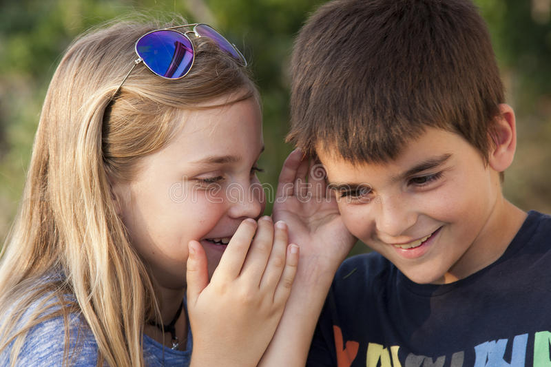 Secret. Boy and girl counting a secret to the ear. instagram effect stock photos