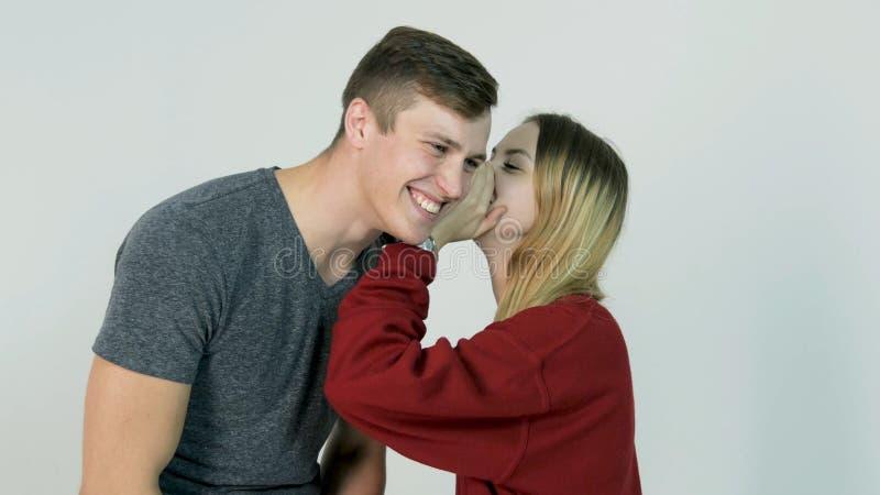 Secret de chuchotement de jolie fille dans l'oreille de son ami riant sur le fond blanc - concept d'amitié photos stock