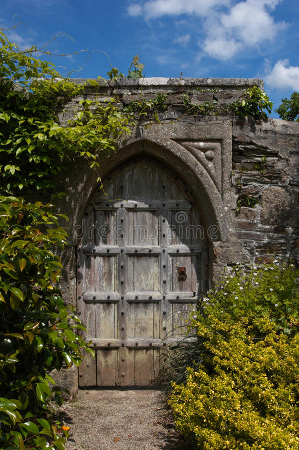 Secret Door To The Magic Garden. Secret door in a garden which might lead to somewhere hidden or magical. An old reinforced wooden door with a mediecal royalty free stock photo