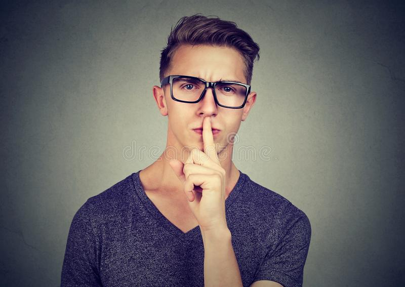Secret guy. Man saying hush be quiet with finger on lips gesture looking at camera. Isolated on gray wall background royalty free stock image